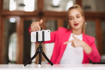 Close up young female blogger recording new video on smartphone