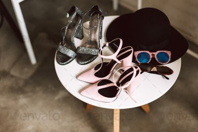 Close up modern shoes on heel,sunglasses and black hat on stand