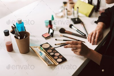 Close up make up artist sitting at the desk withbvariety of cosm
