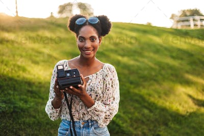 Pretty smiling african girl holding polaroid camera in hands hap