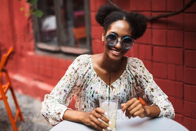 Beautiful smiling african girl in blouse and sunglasses happily