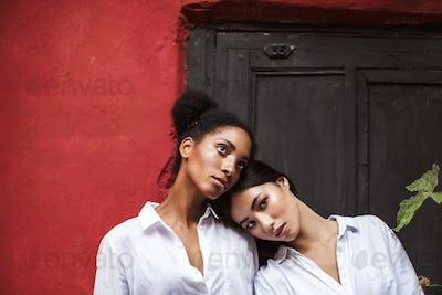 Young beautiful women in white shirts thoughtfully looking aside