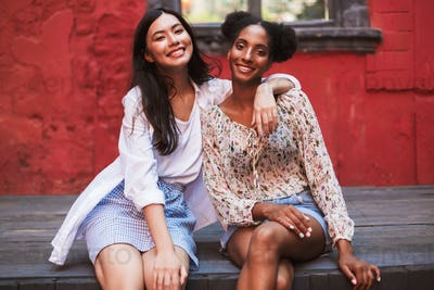 Two beautiful smiling girls happily looking in camera while spen
