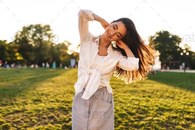 Pretty smiling girl in white shirt joyfully looking aside while