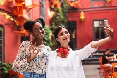 Two pretty stylish girls taking photos on cellphone while happil