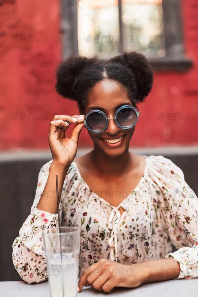 Beautiful smiling african lady in blouse and sunglasses while ha