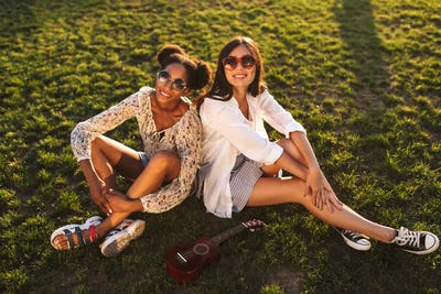 Two pretty smiling girls sitting on grass happily looking in cam