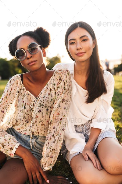 Young beautiful ladies sitting on grass thoughtfully looking in