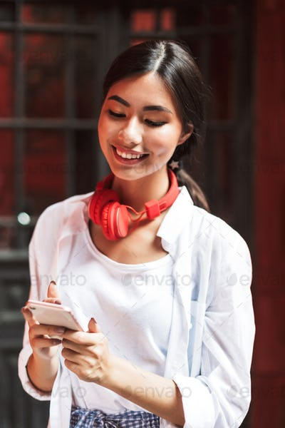 Joyful girl in white shirt and red headphones happily using cell