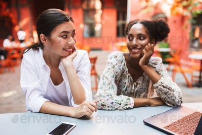 Young beautiful girls joyfully looking at each other while worki