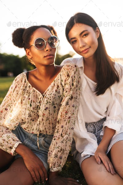 Beautiful girls sitting on grass dreamily looking in camera whil