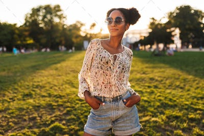Young beautiful african woman in sunglasses dreamily looking in