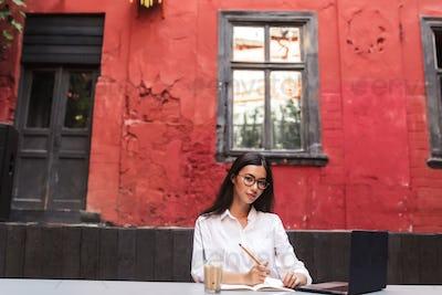 Beautiful girl with dark hair in white shirt and eyeglasses drea
