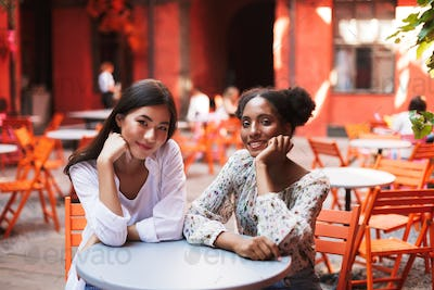 Two beautiful smiling girls leaning on hands dreamily looking in