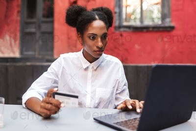 Young african woman in white shirt holding credit card in hand w