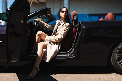 Young beautiful lady in sunglasses and trench coat on heels in c
