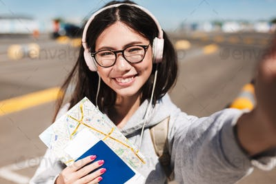 Portrait of smiling girl in eyeglasses and headphones happily lo