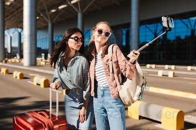 Two pretty girls in sunglasses joyfully taking photo on cellphon