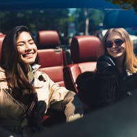 Two cheerful girls happily spending time together driving cabrio