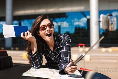 Joyful girl in sunglasses with map leaning on cabriolet car whil