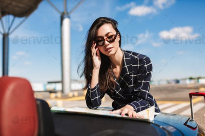 Beautiful girl in sunglasses leaning on car thoughtfully looking
