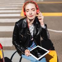 Beautiful girl in headphones listening music dreamily closing ey