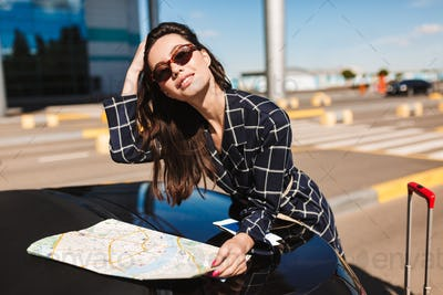 Beautiful smiling girl in sunglasses with map leaning on black c