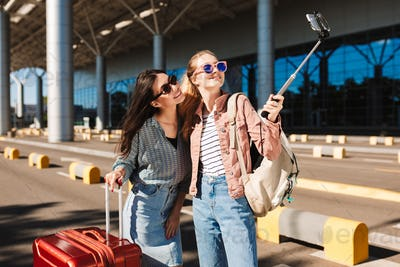 Two pretty girls in sunglasses happily taking photo on cellphone
