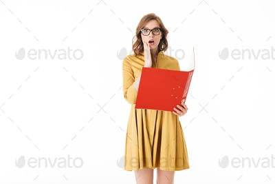 Young lady in eyeglasses and yellow dress holding red folder while amazedly looking in camera