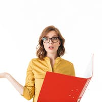 Portrait of young lady in eyeglasses standing with open red folder and amazedly looking in camera
