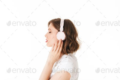 Portrait of beautiful lady listening music in headphones while dreamily closing her eyes