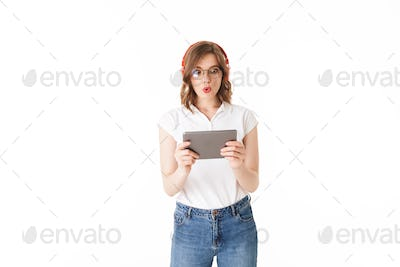 Portrait of young astonished lady in eyeglasses and headphones standing with the tablet in hands
