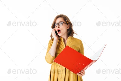 Portrait of young shocked lady in eyeglasses standing with cellphone and open red folder in hands
