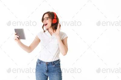 Portrait of young joyful lady in eyeglasses and headphones standing and happily looking in tablet