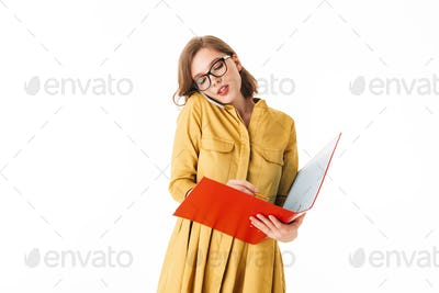 Young lady in eyeglasses talking on her cellphone and thoughtfully looking in open red folder