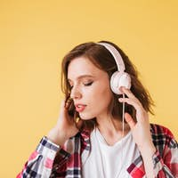 Portrait of beautiful pensive lady in colorful shirt standing and listening music in headphones