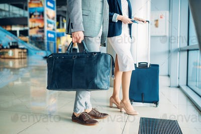 Passengers with luggage in airport, business trip
