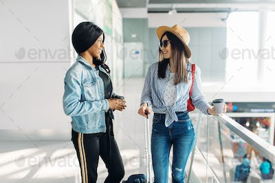 Two female travelers with luggage in airport