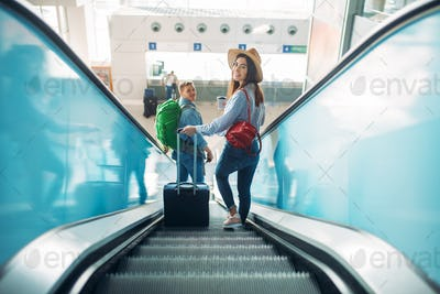 Couple with luggage climb the escalator, airport