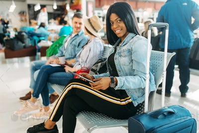 Female black tourist with suitcase in airport