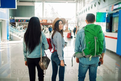 Three tourists with luggage waiting in airport