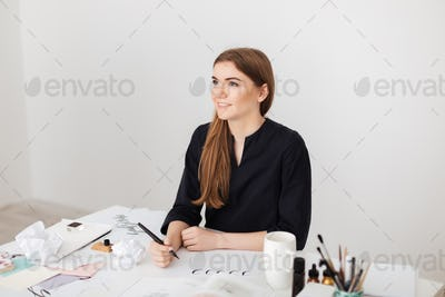 Portrait of young smiling lady sitting at the white desk and writing notes on paper