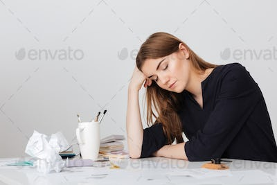 Photo of cute lady sitting at the white desk and sleeping while leaning head on her hand isolated