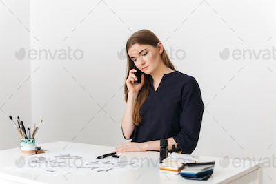 Portrait of young pretty lady sitting at the white desk and talking on her cellphone