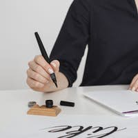 Beautiful photo of young woman hands writing on paper on desk  isolated