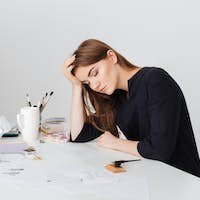 Young pretty lady sitting at the white desk and sleeping while leaning head on her hand isolated