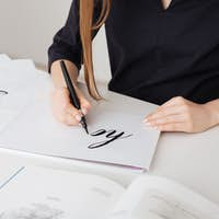 Portrait of young woman hands writing beautiful notes on paper on desk  isolated