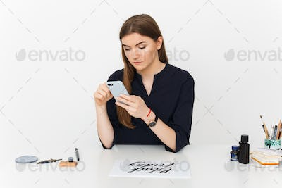 Portrait of young beautiful girl sitting at the white desk and thoughtfully looking in her cellphone