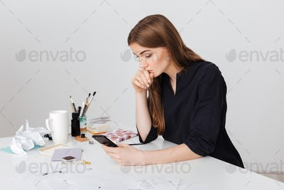 Portrait of young beautiful lady sitting at the white desk and thoughtfully looking in her cellphone