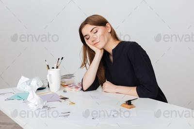 Portrait of beautiful lady sitting at the white desk and sleeping while leaning head on her hand
